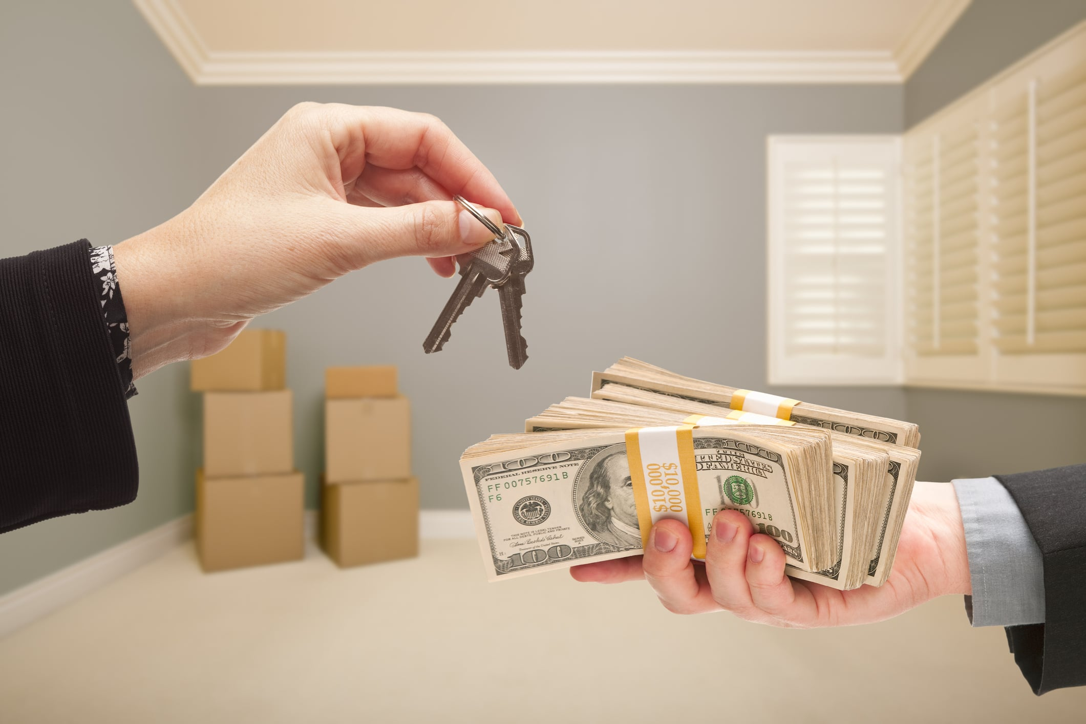 Man and Woman Handing Over Cash For House Keys Inside Empty Gray Room with Boxes.