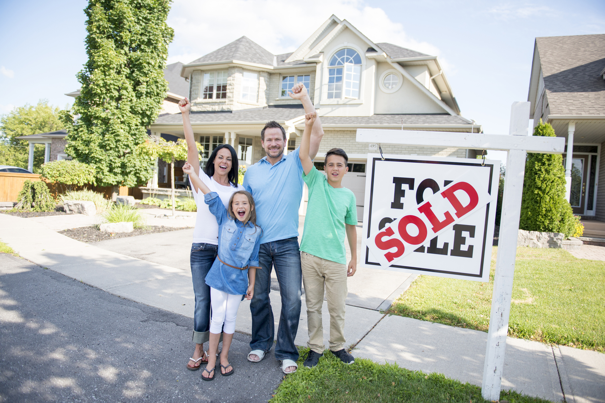 """A family of four are standing outside of their new home. The sign in front of the house says, """"for sale"""" and """"sold."""" They are smiling and looking at the camera."""